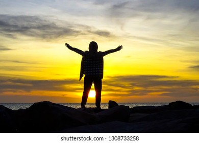 Silhouette of a happy muslim woman with hands raised in the beautiful sunset over the sea.