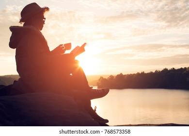 Silhouette of happy old women reading a book sitting on the rock near lake waiting for sunset relax time and holiday, color vintage style selective and soft focus