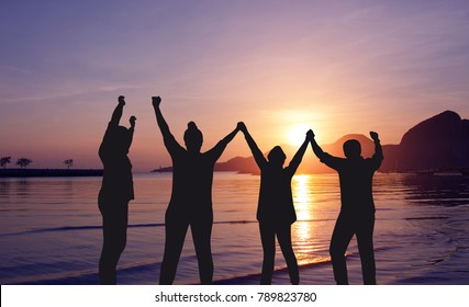 Silhouette of  happy people group on the beach with beautiful  sunrise background,  they are 4 people,hands rise,hands check,jumping, success team concept.