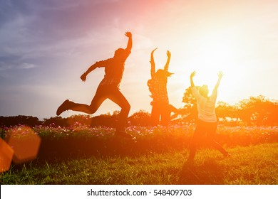Silhouette of happy people jumping in sunset.