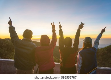 Silhouette of happy people raising their hands with a sun background.