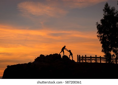 Silhouette of happy people in sunset On the Cliff by the Sea.