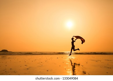 silhouette of happy running woman on the beach