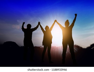 Silhouette of happy teamwork 3 people making high hands over head up to   the beautiful sky background ,business successful, goal achievement ,business victory, business teamwork concept and freedom.