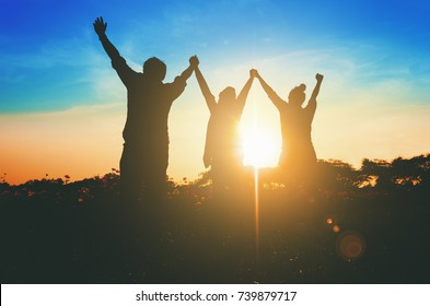 Silhouette of happy teamwork hold hands up as a business successful, business victory. Sun len flare effect