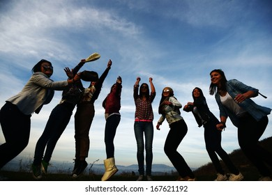 Silhouette of happy teen girls having good fun time outdoors