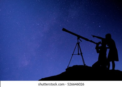 Silhouette happy time of boy and girl with telescope on the rock at the star background