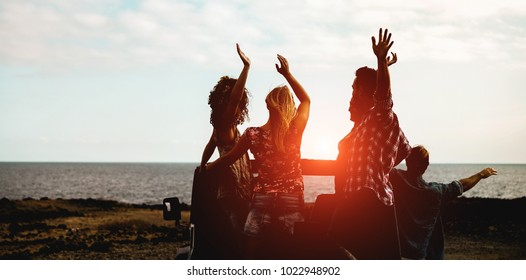 Silhouette of happy tourists friends doing excursion next the beach on convertible 4x4 car - Young people having fun traveling together - Friendship and vacation concept - Focus on center guys