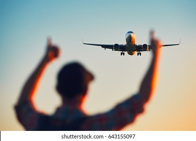 Silhouette of the happy traveler which watching landing of the airplane during sunset.