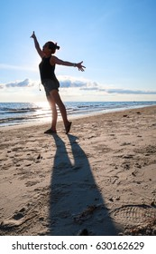 silhouette happy woman dancing at the beach blue sky