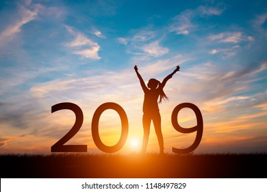 Silhouette of happy woman with New year 2019 concept in sunset background.