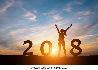 Silhouette of happy woman with New year 2018 concept in sunset background.