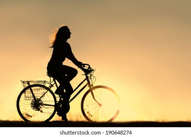 A silhouette of a happy woman outside riding a vintage bicycle, isolated in front of a sunset in the sky.  Copyspace.