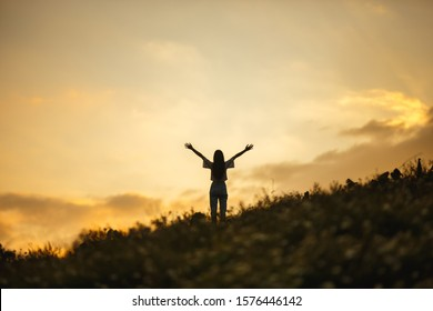 silhouette of happy woman relaxing on mountain hill  in summer sunset sky happy girl enjoying freedom and life raising arms feeling free