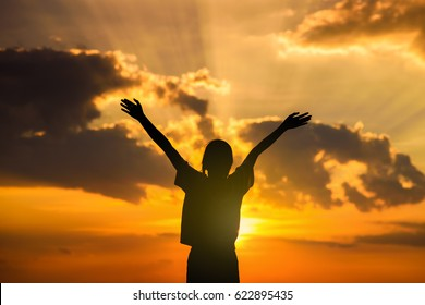 silhouette of happy woman relaxing in summer sunset sky and clouds, blissful girl enjoying freedom and life raising arms feeling free