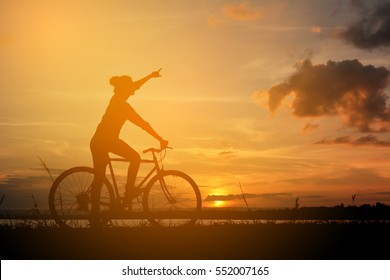 Silhouette of happy women with bicycle in nature at the sky sunset color warm tone