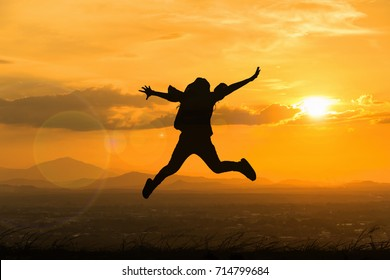 silhouette of happy women jumping in sunset