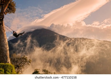Silhouette Of Happy Young Man On A Swing With Tungurahua Volcano In The Sunset Background