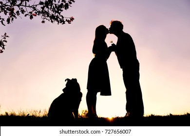 A silhouette of a happy young married couple in love, kissing under an Oak tree, next  to their pet dog outside on a summer night.