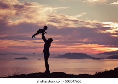 Silhouette of a happy young mother, laughing as she plays with her toddler child and lifts him over her head outside, isolated against the sunset, ocean, fjords and mountains in fog.