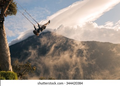 Silhouette Of A Happy Young Teenager Girl Swinging On A Swing Above The Andes Mountains, Tungurahua Volcano In The Background