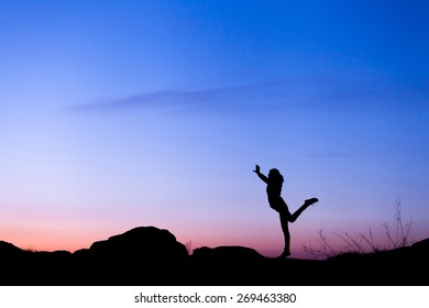 Silhouette of happy young woman against beautiful colorful sky. Summer Sunset. Landscape