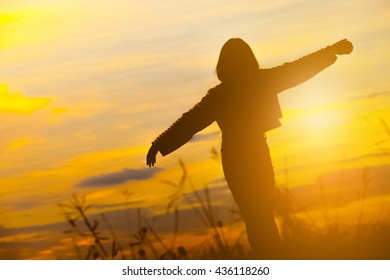 Silhouette of happy young woman over beautiful twilight sunset.
