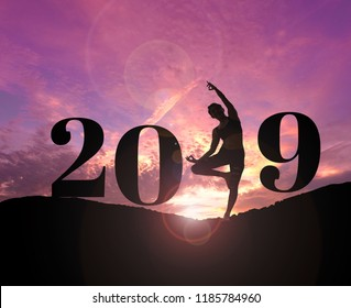Silhouette of healthy young woman practicing yoga on the hill and 2019 years with sky twilight with filter lens flare. concept celebrating new year.