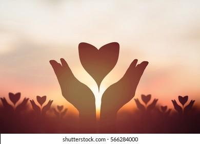 Silhouette  heart over  hand. Background sunrise