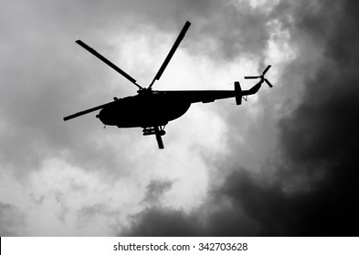 silhouette of a helicopter in the clouds, black and white