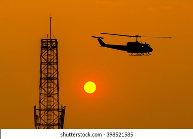 Silhouette of helicopter and communication antenna on sunset.
