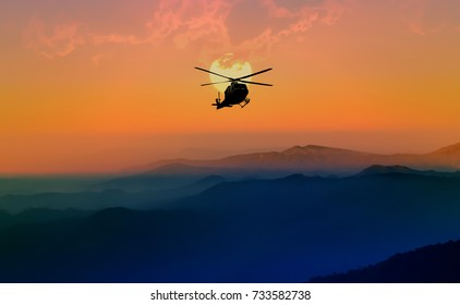 Silhouette helicopter is flying over the mountain while the sun is falling. Silhouette helicopter in sunset background. Helicopter flying in beautiful nature.