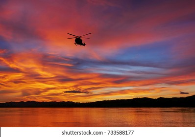 The silhouette helicopter is flying over mountains and rivers while the sunset.