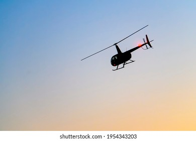 Silhouette of a helicopter on the background of the evening sky.