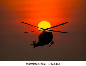 Silhouette of Helicopter on sunset background.