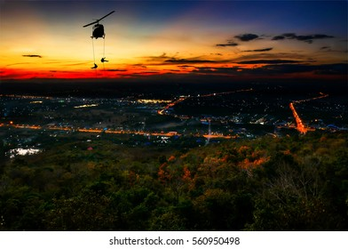Silhouette of helicopter, soldiers rescue helicopter operations on city and sunset sky background.