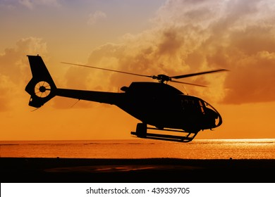 silhouette of helicopter taking off at sunset