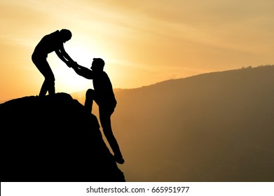 Silhouette of helping hand between two climber - Stock Image