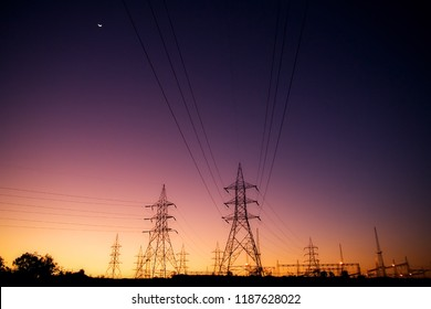 Silhouette High voltage electric towers at sunset time