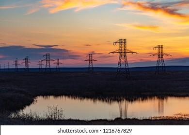 Silhouette of high voltage posts at sunset. Norilsk. September 22, 2018
