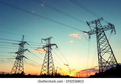 silhouette of high voltage power lines against a colorful sky at sunrise or sunset.