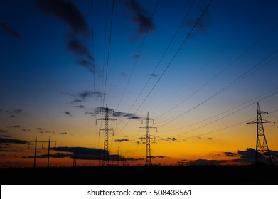 A silhouette of high voltage power lines against a dramatic and colorful sky at sunrise or sunset