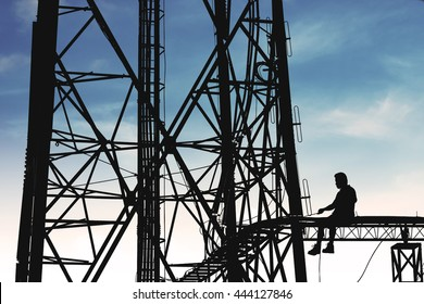Silhouette, high voltage tower, telecommunication tower, TV antennas with worker repairing, maintenance on blue sky with copy space
