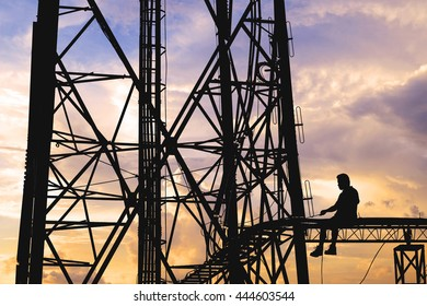 Silhouette, high voltage tower, telecommunication tower, TV antennas with worker repairing, maintenance in sunset