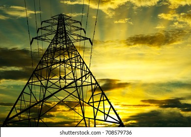 Silhouette of High voltage transmission tower with golden sky background at a twilight time.