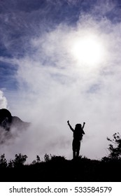 Silhouette of Hiker Celebrating Success with open arms on the top of a Mountain during the Sunrise - Vertical