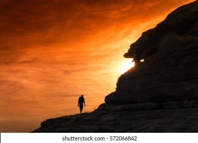 Silhouette of hiker climbing towards sunset with orange glowing sky. Northern Territory, Australia