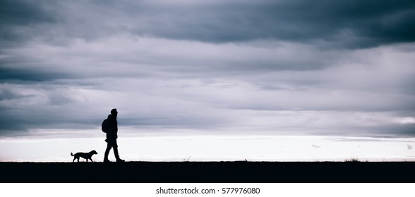 Silhouette of hiker and dog walking together