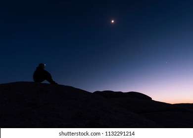 Silhouette of hiker sitting on rock formations with a headlamp lit watching the sunset and the purple and blue sky behind him with stars above in Joshua Tree National Park, California