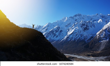Silhouette of hiker standing on a peak of mountain with raised hands and rejoices sunrise above the snowy mountain